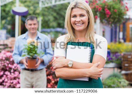 Woman holding a notepad while man holding a potted plant in the garden center - stock photo