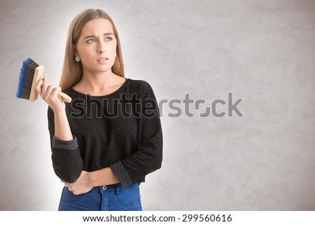 Woman holding a paint brush and wondering - stock photo