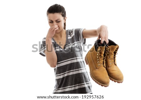 woman holding a pair of men smelly work boots in the air not looking happy - stock photo