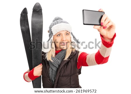 Woman holding a pair of skis and taking a selfie with cell phone isolated on white background