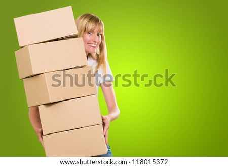 woman holding a pile of boxes against a green background - stock photo
