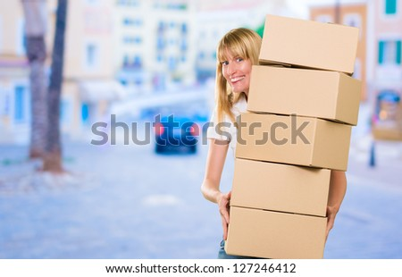 woman holding a pile of boxes against a street background - stock photo