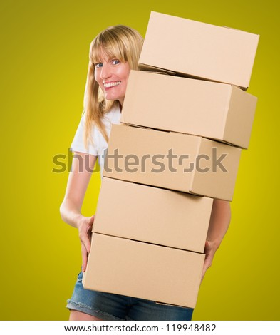 woman holding a pile of boxes against a yellow background - stock photo