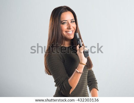 Woman holding a pistol over grey background