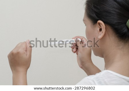 Woman holding a pregnancy test isolated.