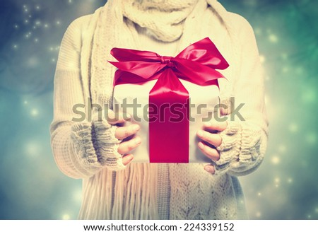 Woman holding a present box in the snowing night - stock photo
