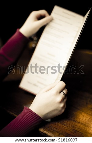 Woman holding a pub menu. - stock photo