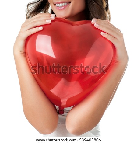 Woman holding a red balloon in the shape of a heart against her body, close-up composition.