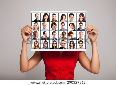 Woman holding a sheet with many people portraits on it - stock photo