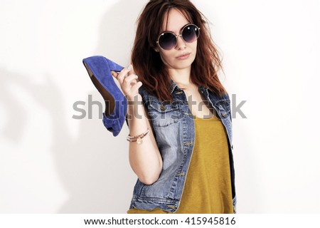 Woman holding a shoe. Women loves shoes concept. Fashion girl and blue high heels shoes. Beautiful young girl  - stock photo