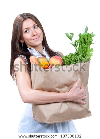 Woman holding a shopping bag full of fresh vegetables, mango, salad, asparagus, radish, avocado, carrots on white background