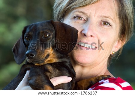 Woman holding a small dog. Focus on woman's face. - stock photo