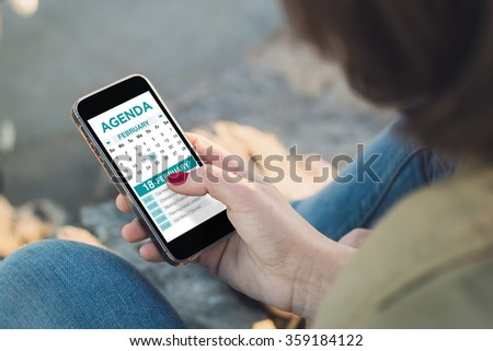 woman holding a smartphone and touching the screen to check agenda. All screen graphics are made up. - stock photo