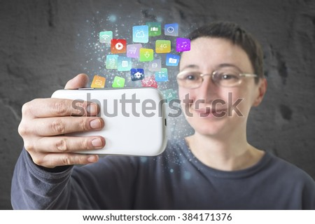 Woman holding a smartphone with modern colorful floating apps and icons. Selective focus.