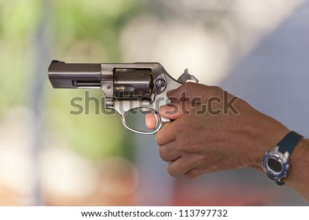 Woman holding a stainless steel revolver, preparing to fire, handgun held in two hand grip, lighting and selective focus on trigger finger. - stock photo