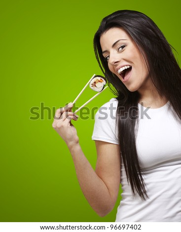 woman holding a sushi piece with chopsticks against a green background - stock photo