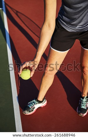 woman holding a tennis ball at a tennis court - stock photo