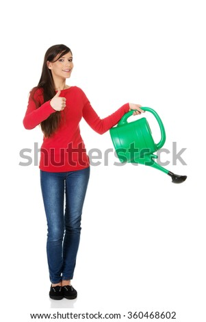 Woman holding a watering can. - stock photo