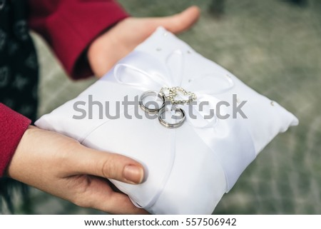 Woman holding a white pad with wedding rings on it