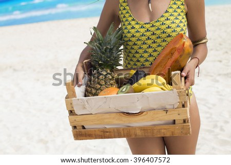 Woman holding a wooden box full of fresh fruit - stock photo