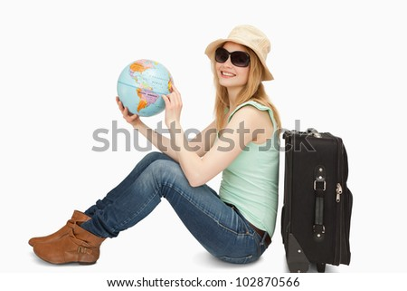 Woman holding a world globe while smiling against white background - stock photo
