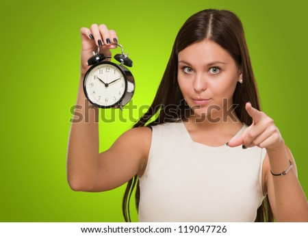 Woman Holding Alarm Clock and pointing against a green background - stock photo