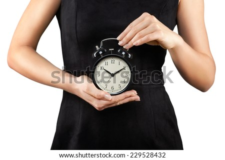 Woman holding alarm clock in hands, isolated on white, time is money - stock photo