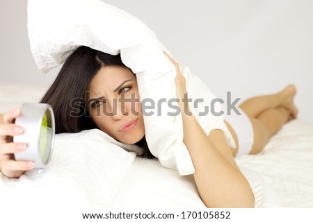 Woman holding alarm clock unhappy - stock photo