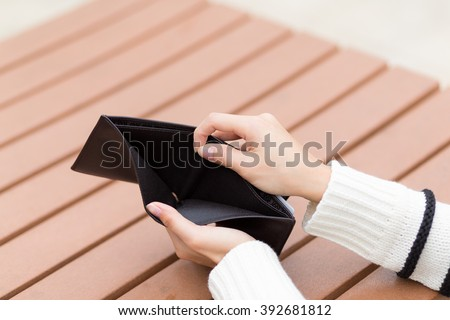 Woman holding an empty wallet - stock photo