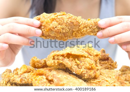Woman holding and eatting fried chicken in white plate on white table - stock photo