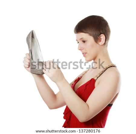 woman holding and looking at a nice shoe, isolated on white