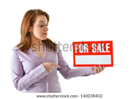 "Woman holding and pointing at ""for sale"" sign - stock photo"