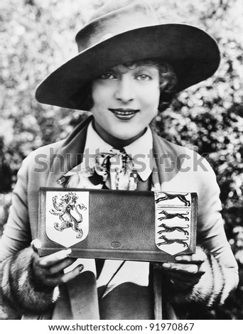 Woman holding and showing a purse with a family crest - stock photo