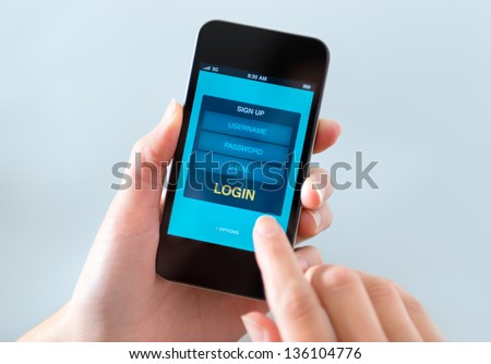 Woman holding and touching on modern mobile smartphone with login form on a screen.
