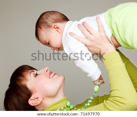 Woman holding baby in hands and raising up high
