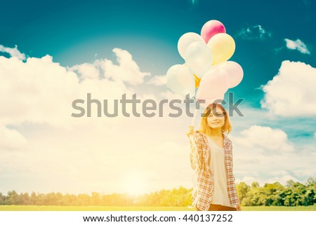 woman holding balloons on meadow and blue sky with sunrise - stock photo