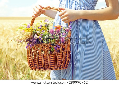 Woman holding basket with beautiful wildflowers outdoors - stock photo