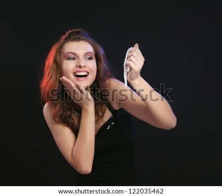 woman holding beads isolated on black background - stock photo