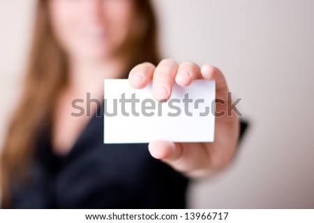 Woman holding blank business card - focus on business card - stock photo
