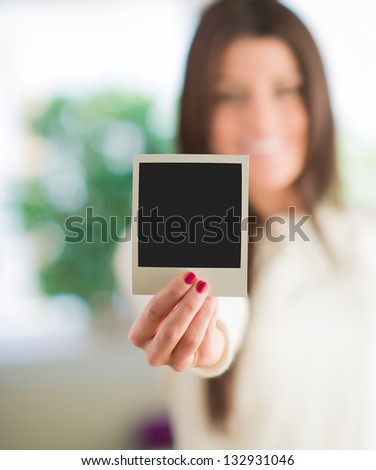 Woman Holding Blank Instant Photo, Indoors - stock photo