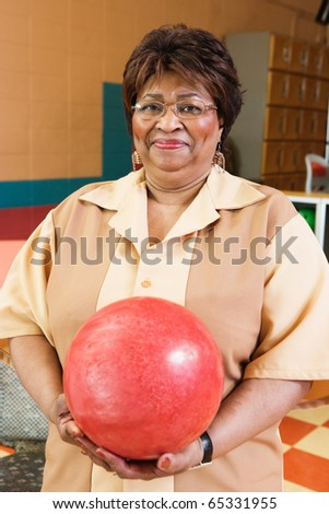 Woman holding bowling ball at bowling alley - stock photo