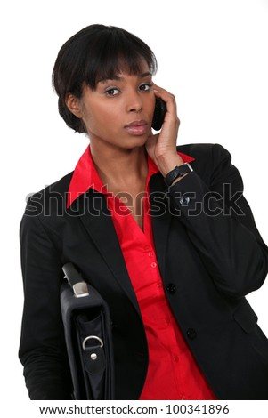 Woman holding briefcase whilst on the telephone