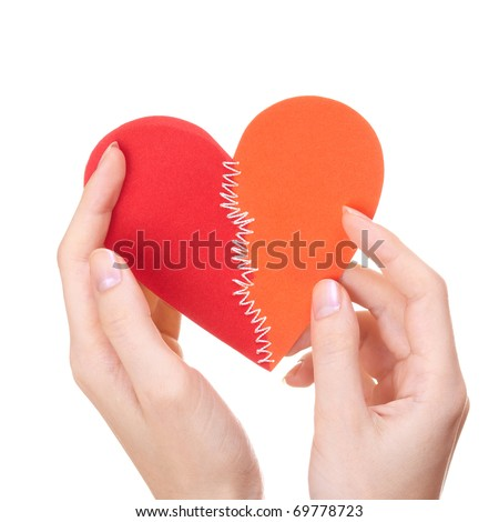 Woman holding broken heart stitched from two pieces in Saint Valentine day - stock photo