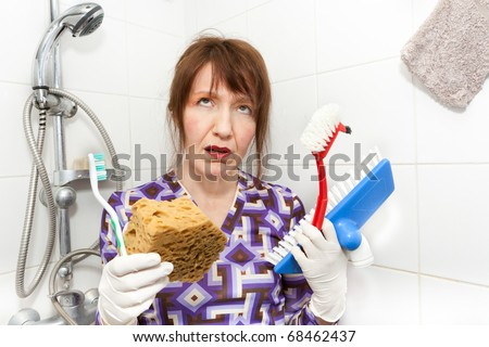 woman holding brushes very bored to clean bathroom shower