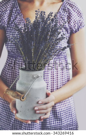Woman holding bunch of lavender flowers in vintage milk churn