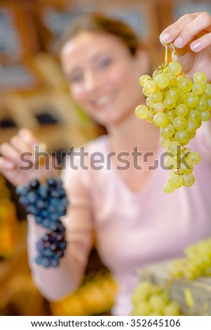 Woman holding bunches of grapes - stock photo