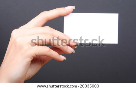 woman holding card on black background