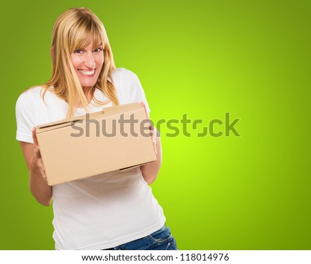 Woman Holding Cardboard box against a green background - stock photo