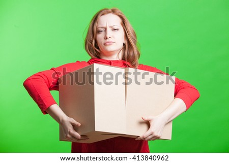 Woman holding cardboard boxes on green background - stock photo