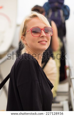 Woman holding carry on luggage queuing to board the commercial airplane. - stock photo